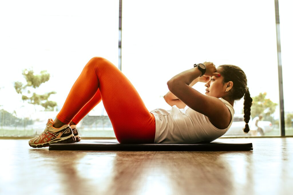 Woman lying on a mat exercising listening to fitness podcast