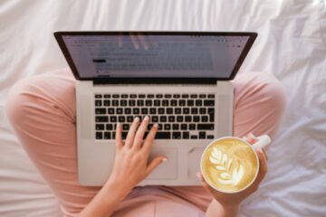 woman working at laptop holding a coffee
