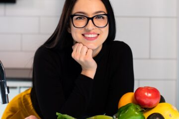 woman smiling with healthy fruit and vegetables in front of her