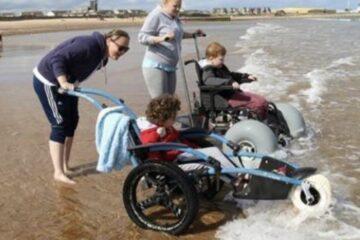 children in wheelchairs on the beach